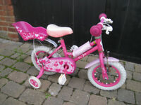 pink child's bike with stabilizers