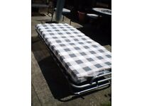Fold up single bed, wood and metal base, castors, mattress. Superb condition. Portable, light weight
