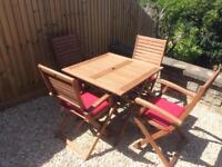 Folding hardwood patio table, four chairs & cushions VGC