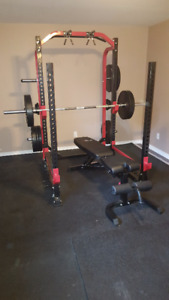 Squat Rack with barbell, weights, bench and gym flooring.