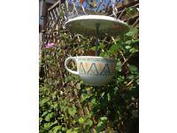 Geometric design teacup and saucer bird feeder.