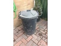Black plastic dustbin, used to store wood in the shed
