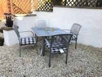 Patio table and four chairs with cushions