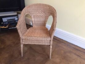 Wicker chair - round backed with decorative pattern.