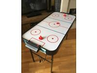 Air hockey table with folding legs for easy storage.