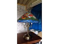 lamp with brass effect stem leading to two candle lights- glass coloured shade
