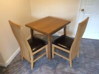 Oak kitchen table and two oak chairs.
