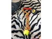 Purple, yellow and orange plaited rope with yellow tennis ball at one end and handle at other end
