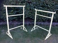 A pair of builder's tresles, refurbished and repainted with red lead primer and yellow top coat.