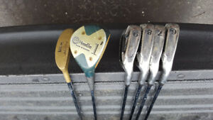 assorted golf clubs and travel bag for sale