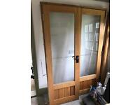 Pair of glass panelled oak doors and frame