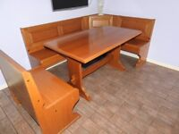 Solid oak dining table with corner seating benches.