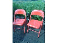 two red retro style metal chairs