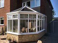 White PVC conservatory with stone foundation in excellent condition