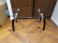 Glass oval coffee table with chrome legs