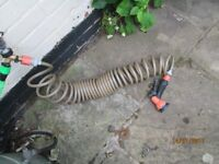 "25' ""Gardena"" super coil garden hose with spray gun."