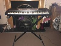 gear4music keyboard with metal stand and 2 music books.