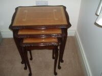 Nest of tables, mahogany with leather patterned glass covered tops.