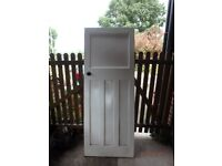 solid wood door with handles .painted white on one side.