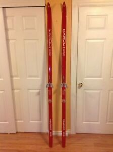Vintage Finnish wooden cross country skis with bamboo poles.