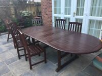 Dark wood patio table and eight chairs. Good condition.
