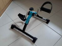 Folding pedal exerciser. For use while sitting to exercise & strengthen legs