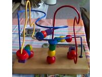 Toy with 3 curly wires on a wooden Base with different coloured and sized shapes that move.