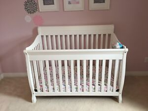 White sleigh crib with mattress and toddler bed railing