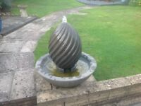Water feature. A cast stone spiral egg pebble bowl fountain water feature