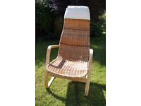 Wicker chair with wooden arms/legs and white fabric headrest cushion