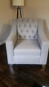 Grey tufted accent chair with studs