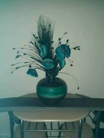 Teal and black vase with flowers
