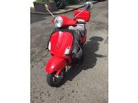 Very low milage reliable red Vespa Lx50 with box and leg cover included