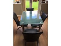Glass table with chrome legs . 4 Black chairs