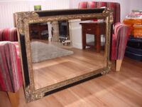 Beautiful large mirror with bevelled edges and a black and gold frame.