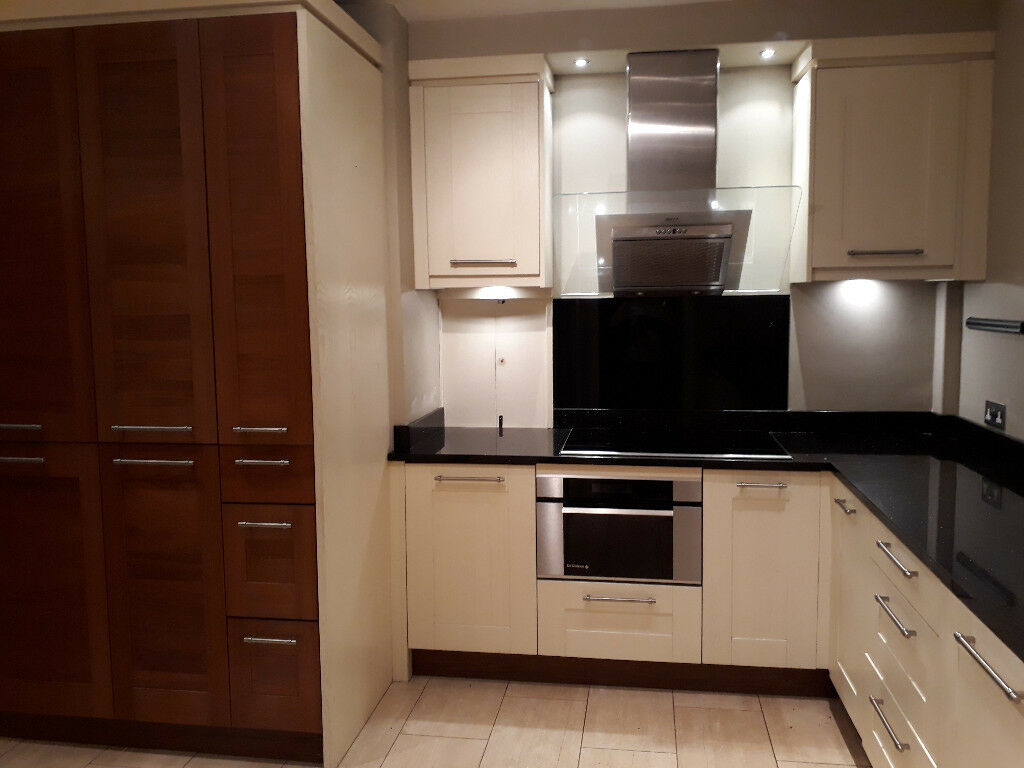 Fitted kitchen with hand painted oak doors walnut veneer tall units and black granite worktop