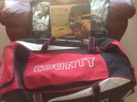 A county cricket bag with back wheels,two pair of cricket gloves ,a boxed ashes book