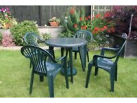 green plastic garden table with four chairs. parasol base,no parasol.