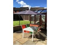 Garden furniture set all -parasol, stylish glass table, coloured chairs and weights included all