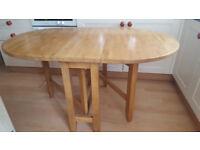 A solid oak drop leaf table
