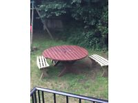 Large round wooden table and four benches