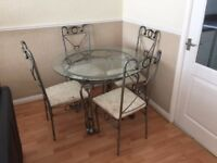 Dining table with metal frame and glass top and 4 padded chairs