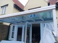 GLASS CANOPY, (cost £2K) for garden patio, nearly new. White aluminium anti-rust. Tinted glass.