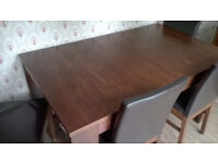 mahogany table and brown material covered chairs extendable