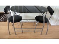 Glass and metal kitchen table and 2 padded chairs