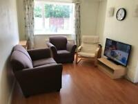 Chocolate brown fabric sofas, IKEA chair and small TV stand
