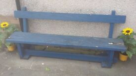 Wooden garden bench which has seen better days, crumbling at the end of seat.