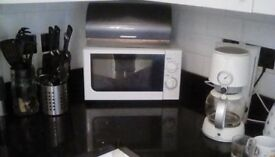 Microwave, plates, pots, filter coffee maker, cutlery, water and wine glasses.
