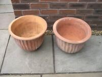 Two terracotta planters with ribbed sides.