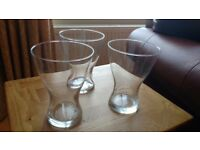 £5 - 3 matching glass vases. Approx 18cm high and 14 cm wide.